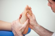 a podiatrist practicing reflexology on a human foot
