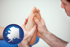 ak map icon and a podiatrist practicing reflexology on a human foot
