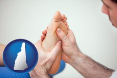 nh a podiatrist practicing reflexology on a human foot