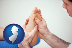 nj a podiatrist practicing reflexology on a human foot