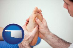 ok map icon and a podiatrist practicing reflexology on a human foot
