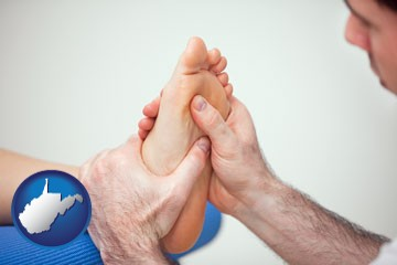 a podiatrist practicing reflexology on a human foot - with West Virginia icon